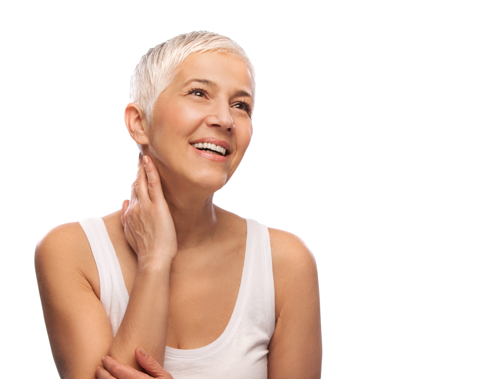 A woman touches her neck and smiles because she used TMJ therapy to alleviate her pain. She has short, white hair and a white tank top in front of a white background.