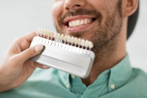 A man receives porcelain veneers, one of our cosmetic dentistry treatments.