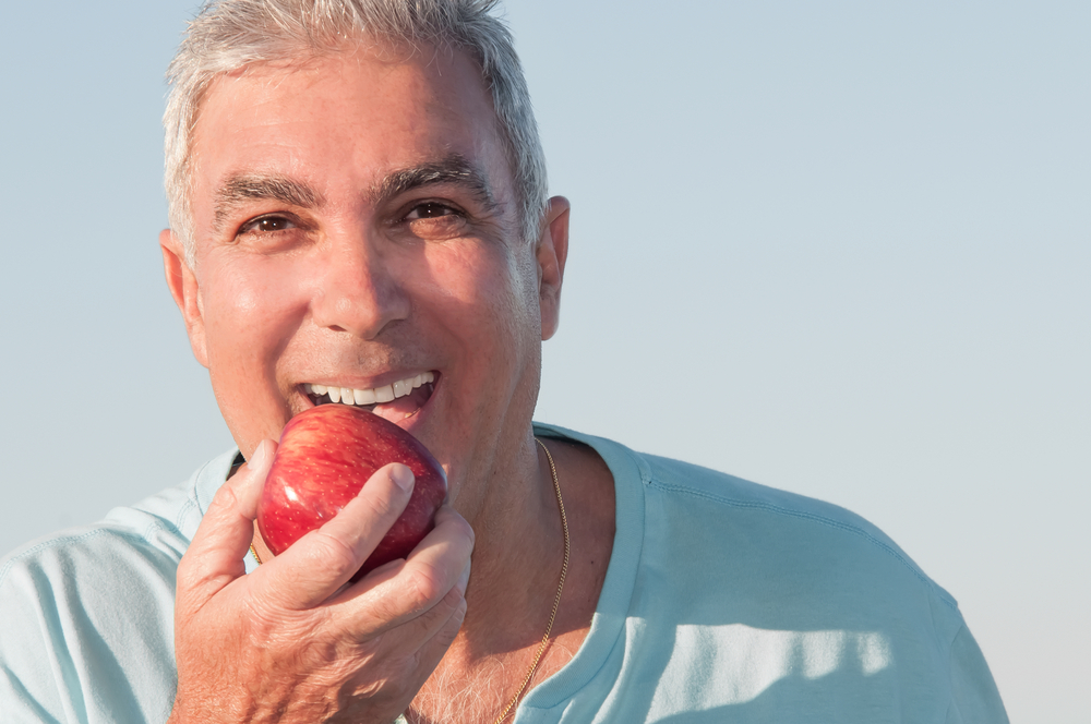 A man is smiling and eating an apple after his TMJ therapy successfully reduced his pain. He's wearing a blue t shirt and has short gray and white hair.