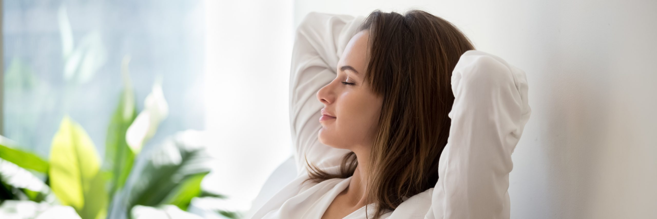 A woman had TMJ therapy and is reveling in the relief in her home. She's wearing a white sweater and resting the back of her head on her hands.