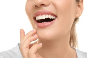 A woman smiles, showing off the results of her dental bonding